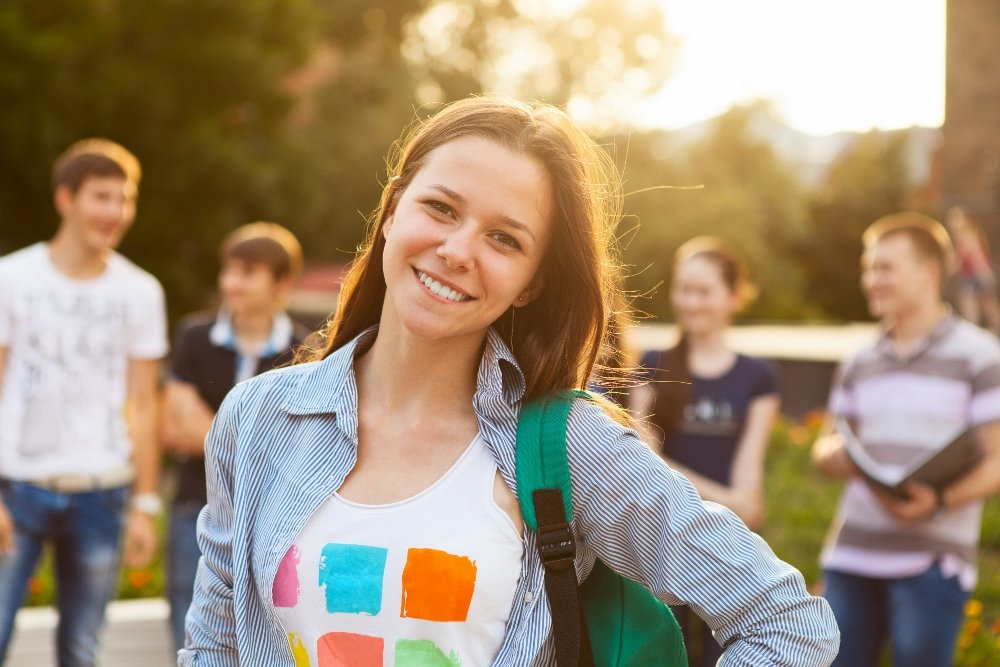 Female smiling student outdoors in the evening with friends